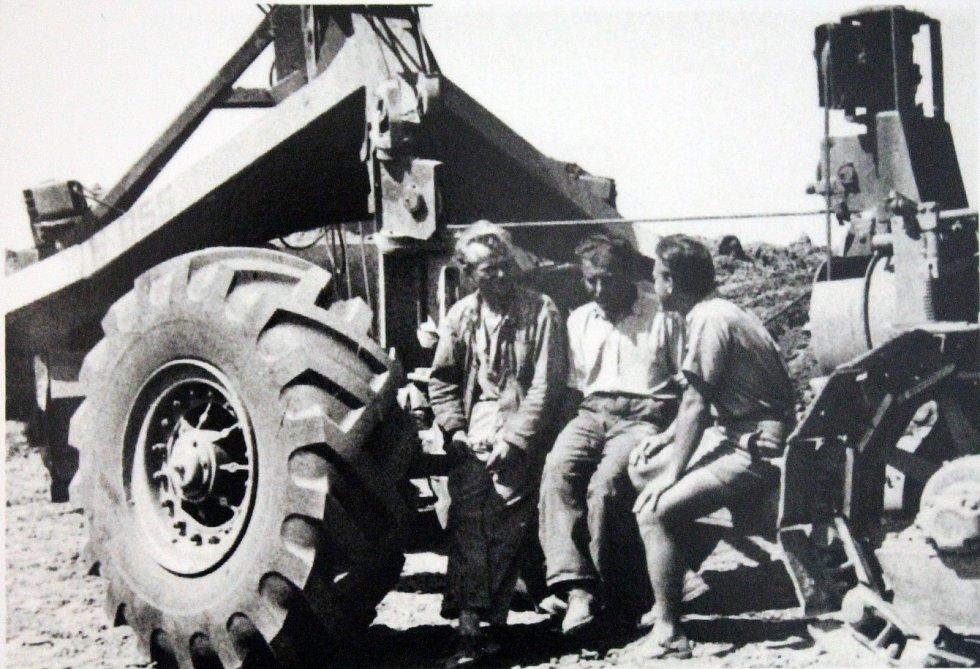 Stavba letiště. Na snímku jsou pracovníci n. p. Posista. Sedící na skrejpru. Skrejpr je těžký pracovní stroj, určený k rozprostírání a přípravě zeminy na velkých plochách, třeba právě při stavbě letiště.