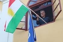 Starosta Okříšek Zdeněk Ryšavý vyvěšuje z okna radnice kurdskou vlajku.