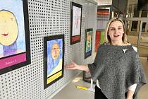 Ředitelka stacionáře Petra Tučková instaluje výstavu ve vstupní hale elektrárny.