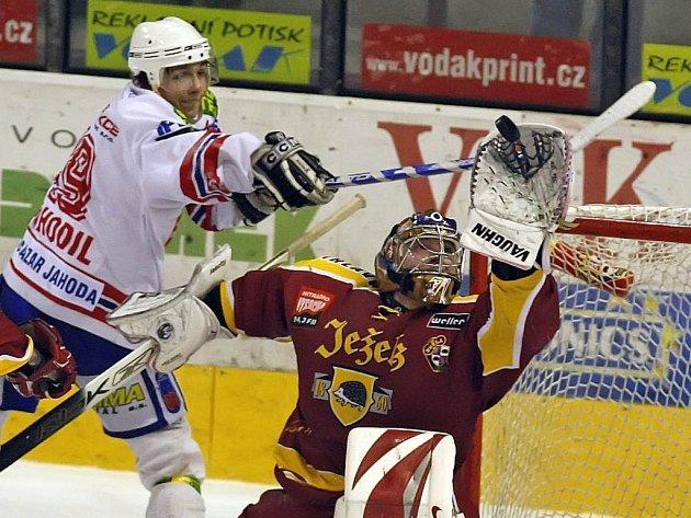Brankář jihlavských hokejistů Milan Řehoř chytá v sobotním prvoligovém zápase puk, který se za jeho záda snažil protlačit útočník Třebíče Lukáš Nahodil (vlevo). Dukla zdolala regionálního rivala 3:2 a poslala ho do bojů o záchranu.