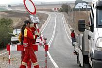 Dělníci stavební firmy odstraňují zátaras, který od června bránil řidičům v průjezdu staveniště. Mnozí očekávali zprůjezdnění hlavní trasy z Třebíče na Moravské Budějovice s velkou nedočkavostí.