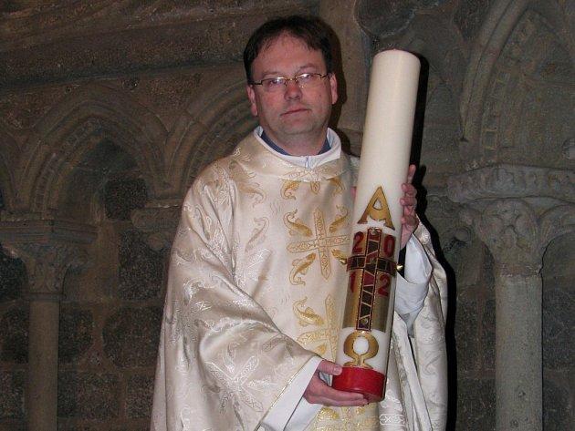 """Farář Jakub Holík z baziliky sv. Prokopa v Třebíči drží v ruce paškál, velikonoční svíci, která bude zapálena při velikonoční Vigilii. Tedy při sobotní noční bohoslužbě, """"která využívá symboliku tmy a světla."""