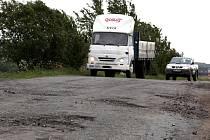 Přes zničenou silnici u Stříteže si krátí cestu nákladní automobily.