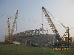 Dva mobilní jeřáby o nosnosti 800 a 650 tun umístily na vybudované mostní pilíře takzvanou výsuvnou skruž, která sama o sobě váží okolo 230 tun.