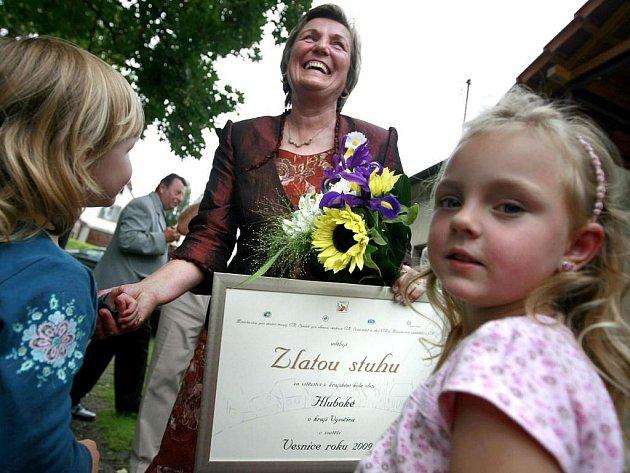 Starostka Hlubokého Marie Svobodová přijímá gratulaci k vítězství v soutěži v roce 2009 od svých vnoučat, Terezky, Aničky a Lucinky.