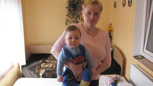 """Hana Fajmonová se svým malým synem na verandě svého domu, ve kterém slyší neustávající zvuky. """"Mám strach o malého,"""" říká."""