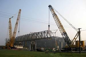 Za ranního kuropění 6. dubna loňského roku obrovské jeřáby umístily na mostní pilíře pomocnou konstrukci pro stavbu mostovky estakády. Most má dnes délku 470 metrů.