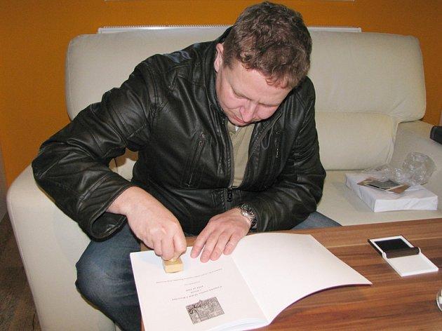 Tomáš Rohovský právě do knihy dává razítko borovinské četnické stanice.