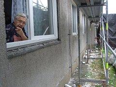 PRÁZDNÉ LEŠENÍ. Lešení je věčně prázdné, dělníci odešli. Visí tam jen jejich blůzy, ukazuje osmdesátiletá obyvatelka panelového domu Marie Hrůzová. Z okna v přízemí se nyní musí dívat na hromadu odpadků.