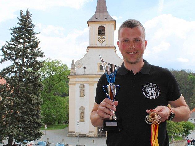 Petr Krátký z  Domu dětí a mládeže v Náměšti nad Oslavou ukazuje pohár a sadu medailí pro vítěze Regionální olympiády dětí a mládeže.