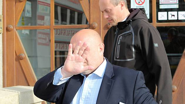 Kněz Mcihal Seknička (v pozadí) odchází se svým obhájcem, který si překrývá tvář od Okresního soudu v Třebíči.