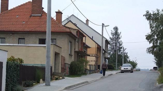 Na pohled běžná ulice s rodinnými domy. Její obyvatelé se ale o ni musí dělit s náklaďáky a autobusy.
