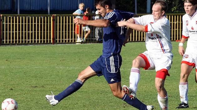 Meziříčský záložník Kamil Průša (uprostřed) se pokouší zastavit útočníka Třebíče Jana Karáska v sobotním divizním derby, které Horácký fotbalový klub vyhrál na domácím hřišti 2:1.
