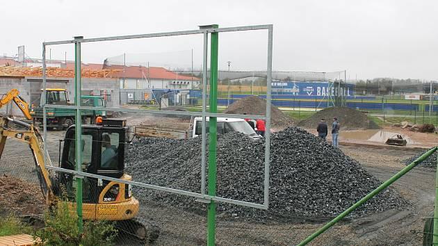 Zatím jsou tam jen hromady materiálu a hrubá stavba obslužné budovy. Kluziště bude v provozu do letošních vánoc.
