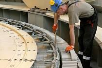 To je kolos. Tři sta tun vážící rotor turbogenerátoru ve vodní elektrárně Dalešice se po kontrole magnetického obvodu vrátil na své místo. Nejtěžší díl v celé elektrárně pomáhaly přemístit dva spřažené jeřáby, každý o nosnosti 160 tun.