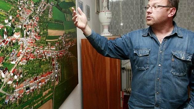 Starosta Rokytnice nad Rokytnou Josef Herbrych vysvětluje u letecké fotografie městysu, proč se zastupitelstvo rozhodlo ukončit členství ve Svazu měst a obcí.