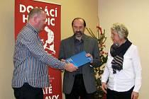 Ředitel firmy OSC předává řediteli charity Petru Jaškovi a vedoucí hospice Evě Vráblové smlouvu o daru.