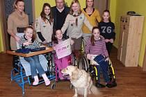 Skautky Anežka Kotrbová a Marie Němcová a starosta Vlastimil Bařinka předávají sestrám Kubíkovým šek. Přihlíží i pes Monty.