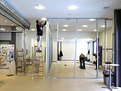 Dělníci staví příčku, která zabrání pronikání prachu ze stavby do výstavních prostor.