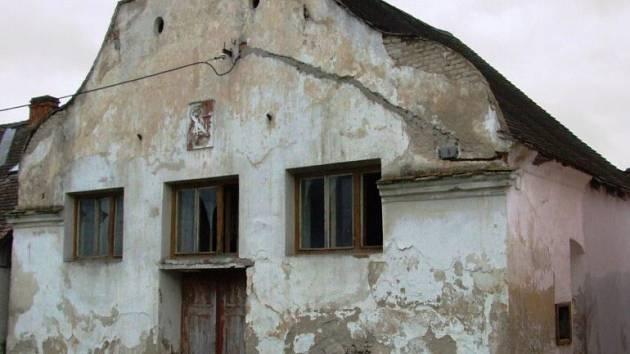Oprýskaný domek s neobvyklým průčelím a vybitými okny. To je nyní bývalá synagoga v Polici u Jemnice.