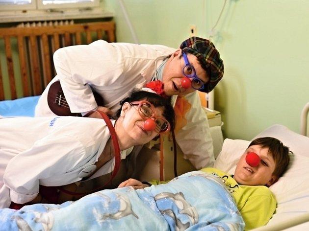 Ve čtvrtek v devět hodin ráno vstoupily na dětské oddělení novoměstské nemocnice tři dvojice profesionálních Zdravotních klaunů. Sestry Vitamínovou, Kotrlou a Vykydalovou s doktory Vitamínem, Naprdovou a Hajným přivítala usměvavá učitelka Katka Nováková,