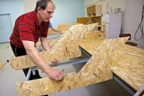 Velkou místnost ve sklepních prostorách Domu kultury ve Žďáře nad Sázavou zatím plní jenom dřevěné desky a trámy. Na ty ale budou časem umístěny stovky metrů kolejí.