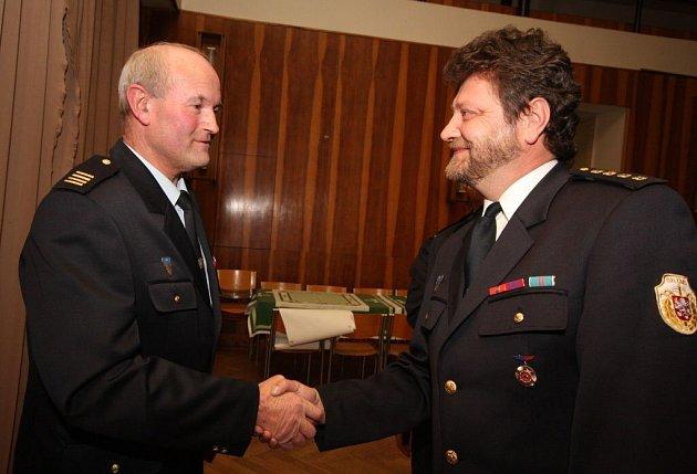 Velitel zásahové jednotky Milan Gamboš blahopřeje kronikáři škrdlovických hasičů Josefu Mrkvičkovi k udělení čestné medaile.
