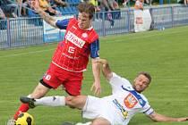 Třebíčský záložník Petr Ošmera (v červeném) se ve včerejším utkání snaží uniknout skluzujícímu kapitánovi Velkého Meziříčí Jaroslavu Krejčímu.