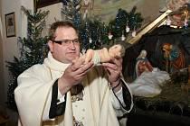 Jezulátko při půlnoční mši uloží kněz do jesliček v betlémě. Ilustrační foto.