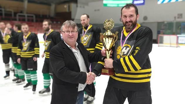 Posledním vítězem Vesnické hokejové ligy se stali loni v březnu hráči Bohdalce, kterým předal vítězný pohár hlavní pořadatel soutěže Karel Daniel (vlevo).