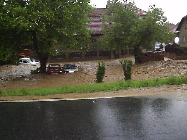 Proud zkalené vody vzal s sebou také zaparkovaná osobní auta.