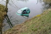 Osobní vůz skončil po nehodě v rybníce. Vyprostit jej musel jeřáb.