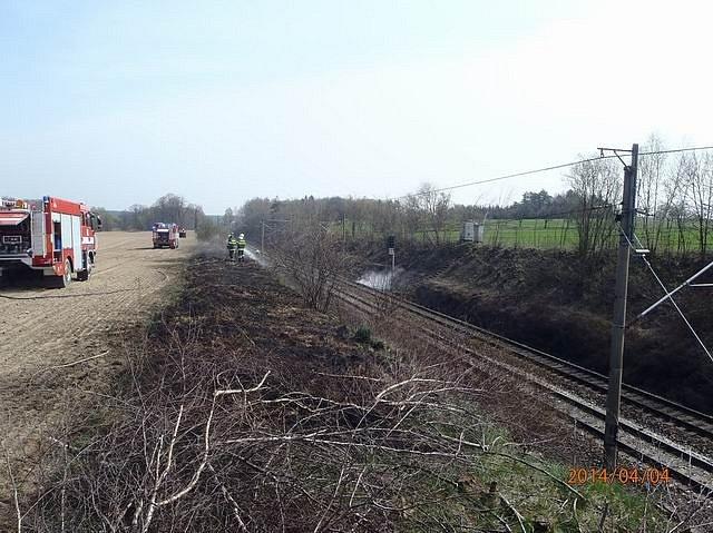 Požár trávy podél železniční tratě u Vlkova.