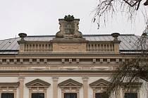 Atiku hlavního průčelí novoměstského zámku zdobí kartuše s erbem a dvě dekorativní vázy. Jedna z nich byla jen provizorně zajištěna.
