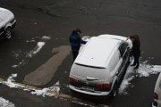 Řidiči ráno odstraňovali sníh z aut.