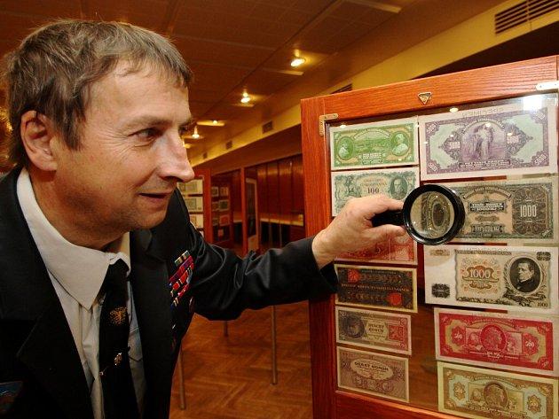 Miroslav Homola si zvětšovacím sklem prohlíží detaily historicky první československé tisícikoruny.