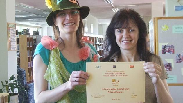Za knihovnického skřítka se včera převlékla knihovnice Olga Kotenová (vlevo)  a s Dagmar Kozlovou, kolegyní z dětského oddělení žďárské knihovny, pak pasovaly prvňáčky na čtenáře. Na snímku drží certifikát za vítězství v soutěži Kamarádka knihovna.