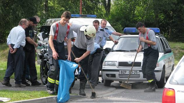 Hasiči uklízejí vozovku po nehodě u historického mostu