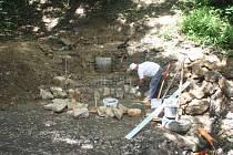 """Střední prostor studny na zachycení vody bude ze zapuštěných skruží vyveden až nad terén, nad ním do svahu budepostavena  opěrná zeď a pod ní zídka s výtokem do oblé malé """"kašny""""."""