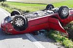 Osobní vůz skončil po nehodě převrácený na střeše.