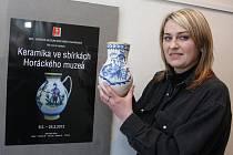Petra Tomášková drží u plakátu výstavy džbán fajáns s modrým dekorem a nápisem světce svatého Petra; džbán byl vyroben ve Velké Bíteši.
