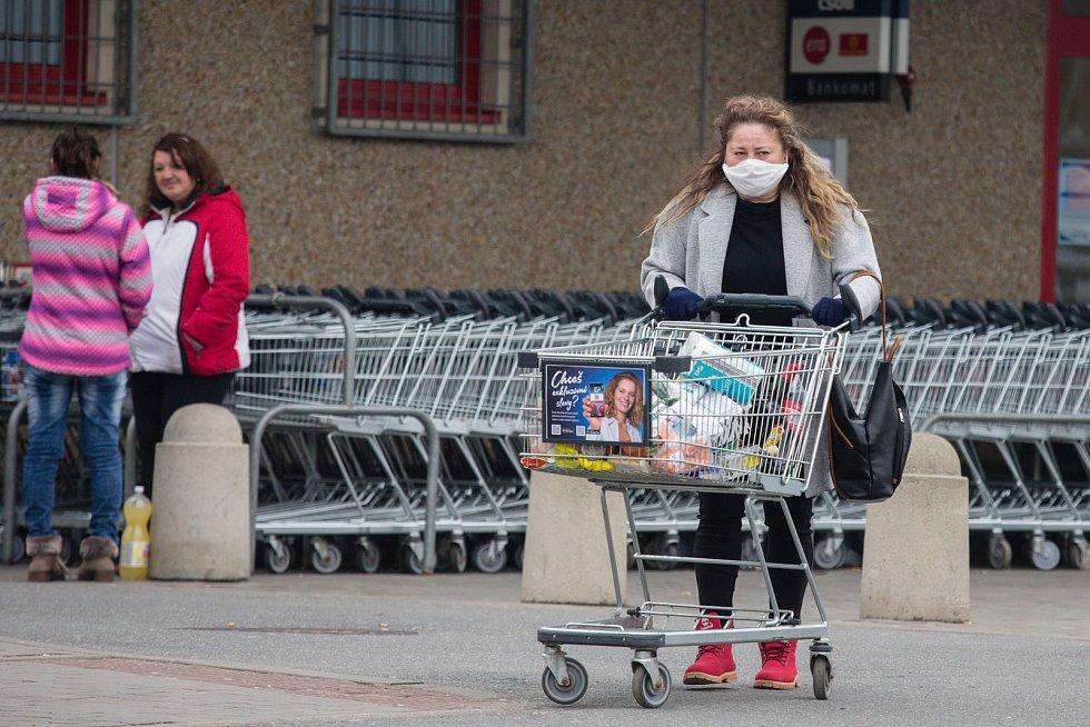 Lidé se při nákupech chrání rouškami a podobnými ochrannými pomůckami.