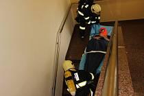 Hasiči vyváželi pacienty v dýchacích maskách ze zakouřené chirurgie. Vyzkoušeli při tom i speciální podložku, pomocí níž figuranta včetně matrace sesunuli po schodišti dolů.