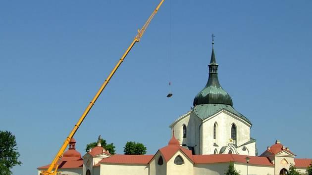 Jeřáb umisťuje trámy na děravou střechu kostela.