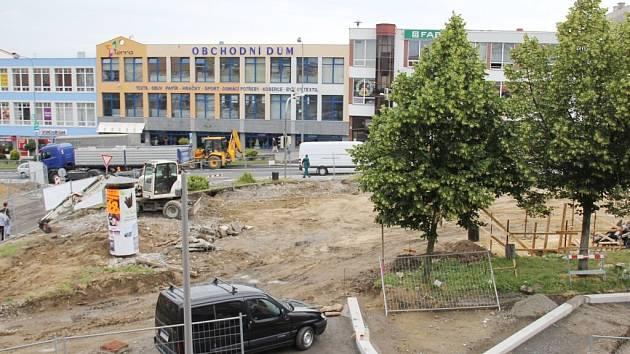 Studna (na snímku mezi stromy v dřevěném oplocení) a lavičky, které budou umístěny okolo tak, aby prostor ohraničovaly, zaberou čtyři parkovací místa. Historický objekt by měl být osvětlený a vybavený bezpečnostní mříží.