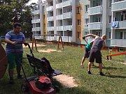 Obyvatelé sídliště posekli dětem trávu u prolézaček.