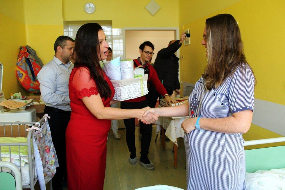 Jednatelka nemocnice Alena Havelková (v červených šatech) při letošní gratulaci mamince prvního letos narozeného miminka v nymburské porodnici.