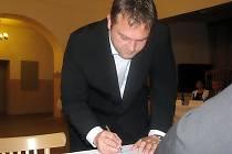 Nový starosta Milovic Lukáš Pilc při podpisu zastupitelského slibu.