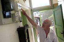 """Karel Žáček u elektrické skříně na verandě svého domu. """"Metr ode mne vyšlehl půlmetrový plamen nebo spíše taková oslepující záře,"""" uvedl Žáček."""