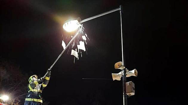 Hasiči při shazování rampouchů z lampy veřejného osvětlení v Nymburce.